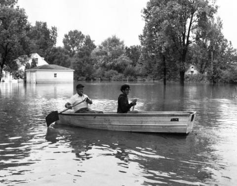 September 1972: Residents of Victory Parkway near Salt Creek in Addison use snow shovels to paddle down the street after a flood.