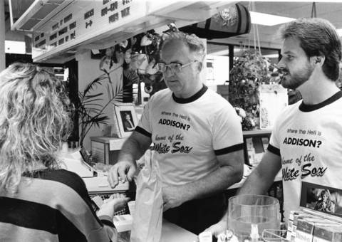 "October 1986: John R. Verstat, owner of Swift Liquor in Addison, is selling T-shirts hailing Addison as the ""Home of the White Sox."" White Sox Chairman Jerry Reinsdorf threatened to move the team from Comiskey Park on the South Side, and Addison was one town lobbying to be the team's new home."