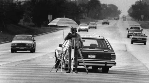 September 1989: Surveyor Henry Sobowiak works in the shade of an umbrella on the median strip at Rohlwing Road and Lake Street in Addison.