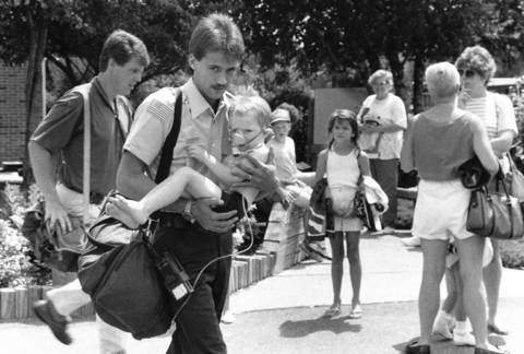 July 1990: A paramedic carries a child to an ambulance after a chlorine gas leak that was caused by an electrical problem in Addison.