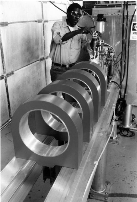 April 1992: Argonne National Laboratory technician David Jefferson installs coils on the test stand for the electron gun and particle accelerator at Argonne's Advanced Photon Source. Electrons produced by the gun will be converted to positrons (electrons with a positive charge) and accelerated to produce the world's most brilliant X-ray beams for investigating materials ranging from semiconductors to the AIDS virus.