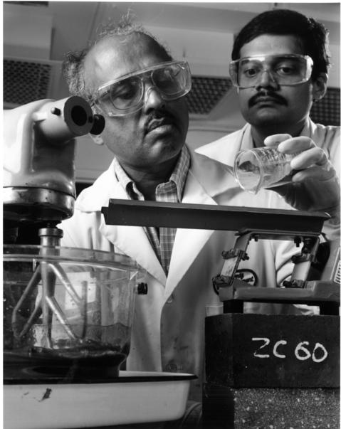 January 1995: Argonne National Laboratory scientists Arun Wagh, left, and Dileep Singh can make a construction material twice as strong as concrete from ashes left from incinerated garbage. The ash can be mixed with magnesium oxide and phosphoric acid to produce a cement-like paste that can be poured and shaped, just like concrete.