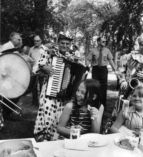 June 1972: The Berwyn Kiwanis club entertains at a picnic for children with disabilities in Proksa Park, where burgers and drinks were served along with songs from a clown band.
