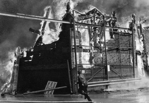 April 1977: A man flees the intense heat of a fire at Berwyn Lumber Co. as the company office collapses in flames near him. Damages were estimated at more than $1 million.