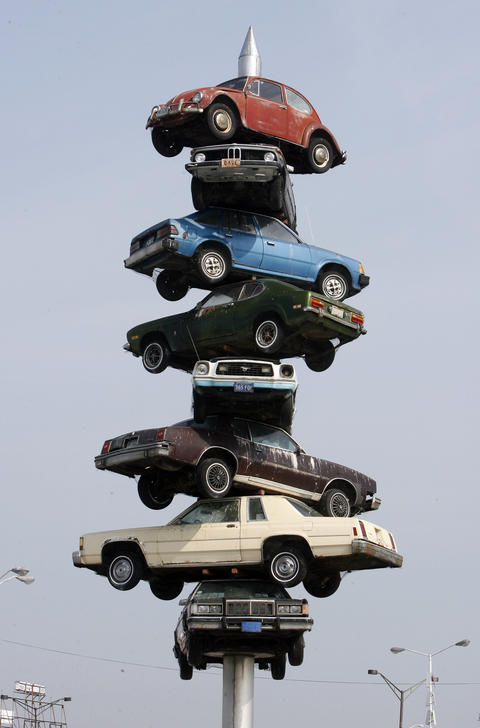 """July 2007: The """"Berwyn Spindle,"""" consisting of eight cars on a giant spike, sits in the middle of the Berwyn Cermak Plaza near Cermak Road and Harlem Avenue. The sculpture, erected in 1989, was razed in 2008."""