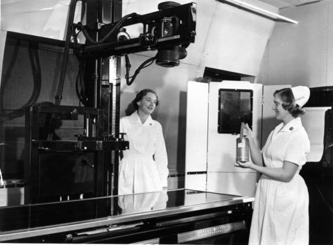 April 1954: Lois Mellquist, right, a nurse at Argonne National Laboratory, shows Argonne's newly-developed portable X-ray unit to Betty Van Dolah, a medical technologist. The unit is small, inexpensive and does not require an electrical power supply. Exclusive of irradiation charges, the total cost of the first model was $40. It provides rays which are comparable in energy to a 100,000 volt X-ray machine.