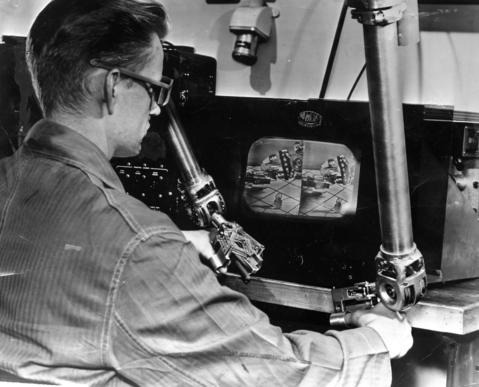 February 1959: Carl A. Hermanson wears 3-D glasses and uses 3-D television and remote-control mechanisms to manipulate a slave robot's arms at Argonne National Laboratory.