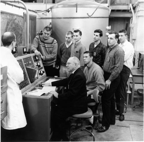 May 1964: Father Marzano is operating the Institute Training Reactor at Argonne National Laboratory while Lewis College students and Argonne staff member, Mr. Ken Ruzich, observe. Left to right (standing): Mr. Ken Ruzich, staff member at Argonne; Frank Stonemark, Chicago; Fritz Kohesh, Hopkins, Minnesota; Joseph Synovic, Lockport; Harold Redelsperger, Chicago; Charles Voelker, Joliet; and Richard Kramer, Chicago. Left to right (seated): Father Marzano, Carl Udovich, Joliet.