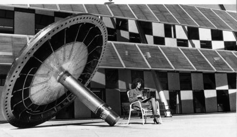 October 1985: Mary Berillo, an executive secretary at Argonne National Laboratory, takes her lunch break in front of a piston that was once used in conjunction with the lab's high energy physics experiments. Constructed of stainless steel, the device was housed in a 12-foot bubble chamber.
