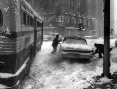 A CTA bus, southbound on Michigan Avenue at Walton Street, sits at an acute angle across the street, immobilized on the slippery pavement on Jan. 26, 1967. Nearby, a policeman tries to aid a motorist.