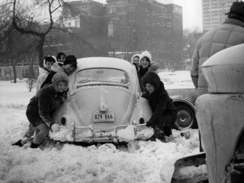 Teenage girls try to help a tow truck rescue their Volkswagen Beetle from a snow drift at the intersection of Stockton Drive and Diversey Parkway on Jan. 27, 1967.