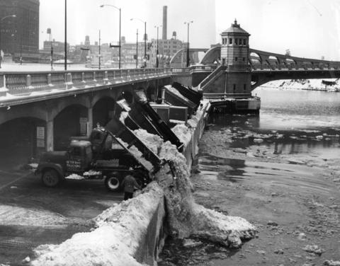 Huge dump trucks operated by city crews offload tons of snow into the Chicago River near Wells Street and Wacker Drive on Jan. 28, 1967.