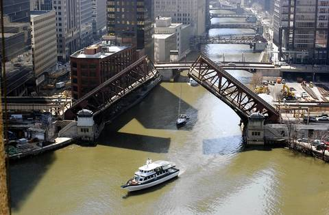 The boat Eleanor R, followed by the sailboat Guppy, pass under the Lake Street Bridge on the South Branch of the Chicago River on their way to to the lake as the bridge opening season begins April 11, 2002.