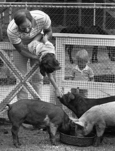 July 18, 1989: Paul Wagner holds his daughter Elyse, 3, as she tries to touch a pig.