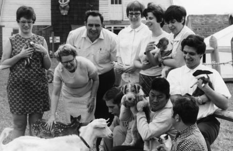 "May 3, 1971: Corinne Owen (second from left) and Robert Terese (behind her) pet animals with the workers who help run the farm. The work at Lambs Farm is touted as an alternative to ""busy-work."""