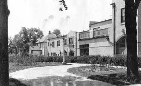 "July, 1929: The caption for this photo of the Public Service Company of Northern Illinois building in Libertyville, states that the ""corporation has made a beauty spot out of ground ordinarily an eyesore through piles of rubbish and dirt."" The photo has rippled due to age and the black smudges above the building show it was once carelessly handled by someone with ink-strained fingers."
