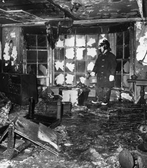 Jan., 1967: A fireman inspects what's left of the living room in the air base home of Rear. Adm. Richard L. Fowler, the head of the Navy's air reserve training program. Fowler was killed in the blaze along with his wife and two children.