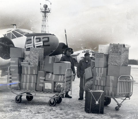 Dec., 1964: One of three planes hauling food, clothing and Christmas presents is unloaded at Rhinelander, Wis., by naval officers and enlisted men from Glenview Naval Air station. The air lift to Rhinelander was met by members of the Chippewa tribe, who transported donations to the Lac Du Flambeau Indian reservation.