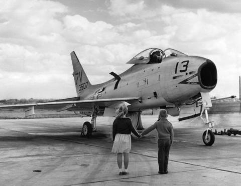 Sept., 1963: Kim and Jeff Stewart of Aurora view the type of Navy jet fighter plane that crashed into a Northbrook home the previous day. The pilot ejected himself from the jet before the crash, and while the home was destroyed, no one was injured. The jet missed Glenbrook North High School by just a few blocks.