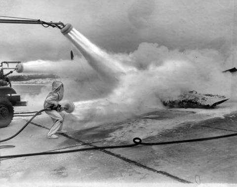 Feb., 1947: A Navy firefighter uses a carbon dioxide vapor spray to snuff out a fire in a plane in an exhibition. The show was seen by 28,000 people.