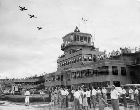 July, 1946: Part of a crowd of 45,000 watch a flight of fighters from the operations tower and the main hangar during an open house.