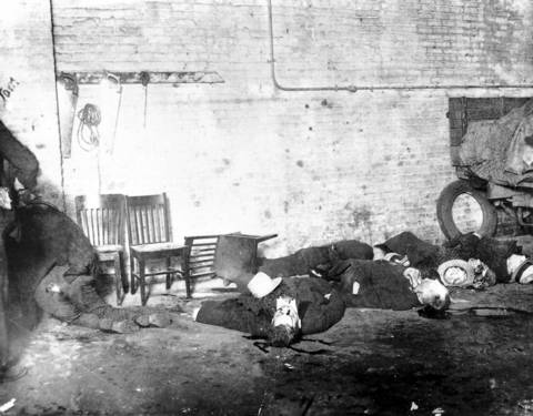 """The bodies of six of the seven men slain on Feb. 14, 1929, in the S. M. C. Cartage Company garage at 2122 N. Clark St. on Chicago's North Side in what became known as the St. Valentine's Day Massacre, sprawl on a floor and a chair. Several of the dead were members of a North Side gang run by George """"Bugs"""" Moran, who had a rivalry with Al Capone and his gang."""