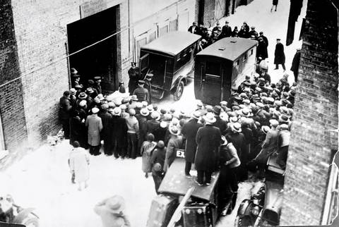 A crowd gathers in the alley behind 2122 N. Clark St., as police remove the victims of the St. Valentine's Day massacre.