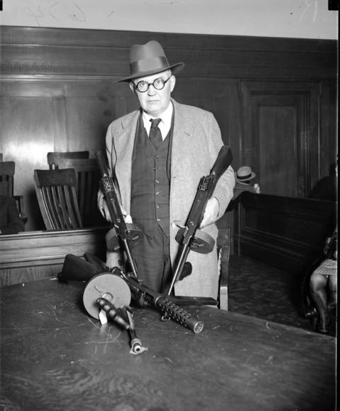Capt. William 'Shoes' Schoemaker shows four machine guns at the inquest for the St. Valentine's Day Massacre on April 19, 1929. Coroner Bundesen had summoned all firearm dealers in the area who had been known to sell machine guns to the coroner's jury in Chicago.