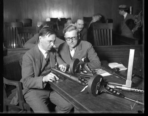 On April 19, 1929, Coroner Herman N. Bundesen, right, and Lt. Col. C. H. Goddard look over machine guns believed to be used in the St. Valentine's Day Massacre. Coroner Bundesen had summoned all firearm dealers in the area who had been known to sell machine guns to the coroner's jury in Chicago.
