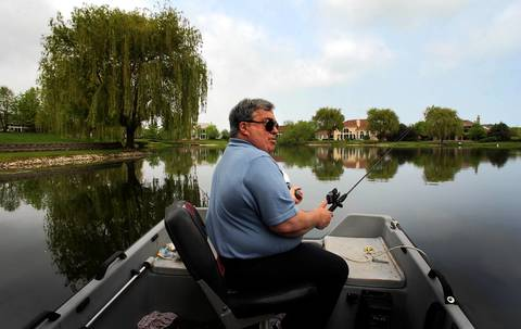 Former Bulls GM Jerry Krause tools around in an electric boat as he fishes in a lake behind his Highland Park home in 2003.