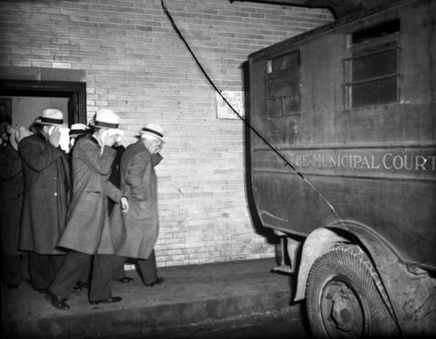 """Police shuttle suspected hoodlums from the detective bureau to a patrol wagon and eventually on to the Criminal Court Building, circa November 1932. The detective bureau raided several establishments on Nov. 2 and 3, 1932, rounding up lawbreakers. They managed to roust 12 of Chicago's most impressive gangsters, including the big boss """"Three Fingered Jack"""" White, and several men who were said to work for Al Capone."""