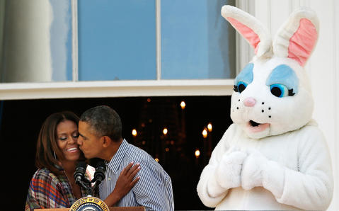 President Barack Obama kisses first lady Michelle Obama at the annual White House Easter Egg Roll on the South Lawn on April 21, 2014.