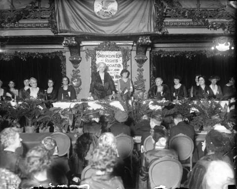 A suffragette convention at the Congress Hotel in Chicago. The speaker at the table is Mrs. Carrie Chapman Catt (standing), a woman's suffrage leader who served as the president of the National American Woman Suffrage Association and was the founder of the League of Women Voters and the International Alliance of Women. Chapman Catt created a suffrage headquarters at the Congress Hotel. Undated photo.