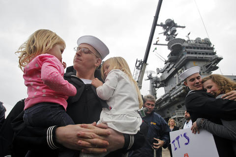 Petty Officer 1st Class Tim Walden holds his two-year-old daughter, Teagan, left, and three-year-old daughter, Zoe, right, after the USS George Washington arrived at Naval Station Norfolk Thursday morning December 17,2015.