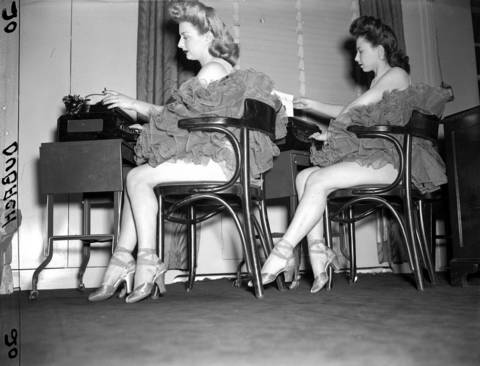 Showgirls Betty Lee Foote, left, and Eileen McDermott work at the Edgewater Beach Hotel's office typewriters between shows in 1944.