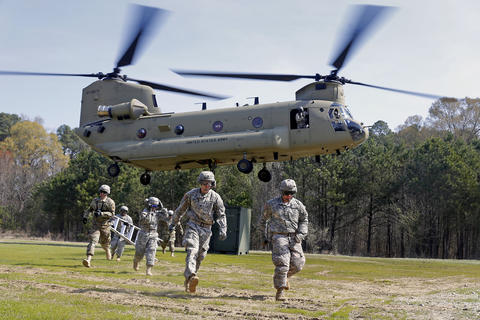 A CH-47 Chinook helicopter hovers above a cargo load at Ft. Eustis Thursday morning as soldiers from the 689th Rapid Port Opening Element practice sling loads and medical evacuations with pilots of the 11th Aviation Command.