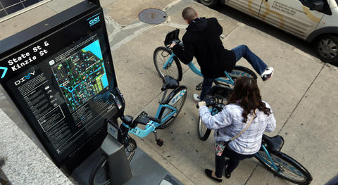 Divvy cyclists rent bikes on Kinzie Street just east of State Street on the Near North Side on April 13, 2016.