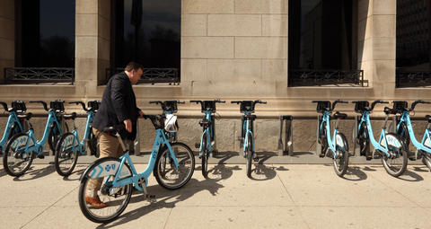 A Divvy bicyclist returns his bike on Michigan Avenue just south of Randolph Street on April 13, 2016.
