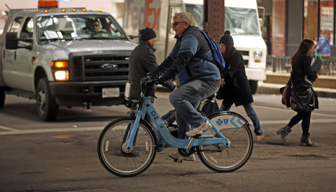 A Divvy bicyclist rides through the intersection of Randolph Street and Wabash Avenue on April 13, 2016.