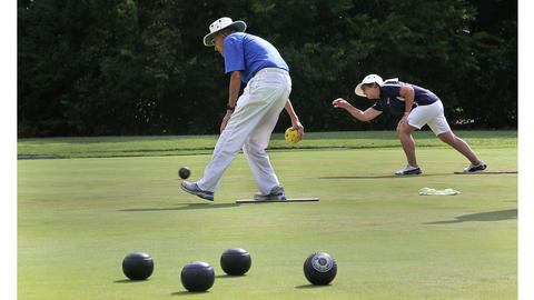 Ready to swing the bowl is Jack Edwards, Willliamsburg, as Rusty Hein, Pittsburgh, rear, has already started her bowl rolling down the lawn. Lawn Bowling's Northeast Division Open Tournament began last weekend.