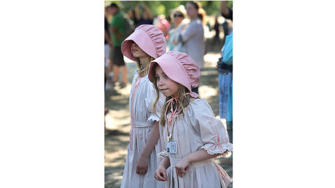 From left, Serena and Ashley Crowley, wearing colonial-style garb, lean in to see a marching regiment pass by. The sisters are visiting from Charlottesville with their parents.