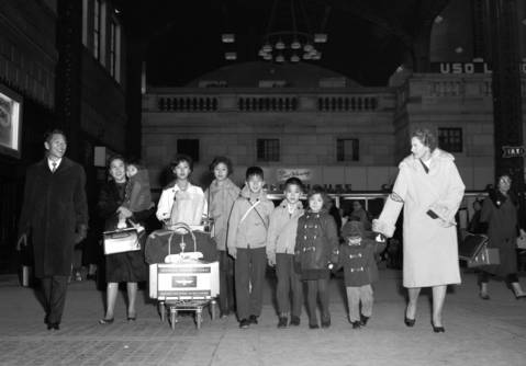 Chinese refugees Thomas Ching Lee and his wife, Wang Su-Ching, arrive with their children at Union Station en route to New York in 1963. The family was helped by volunteer Mrs. Hiram Russell, right.