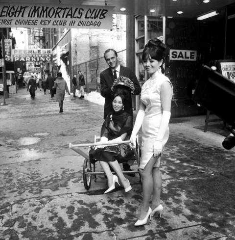 Actor Bob Newhart, center, crowns Miss Judy Chen, 22, winner of the Oriental Queen Contest, while last year's queen, Diane Lee, right, pulls Chen in a rickshaw outside the Eight Immortals Club in Chicago in 1967.