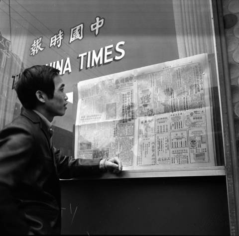 A resident of Chinatown catches up on the latest news from a newspaper posted in the window of The China Times at Cermak Street and Wentworth Avenue in 1970.
