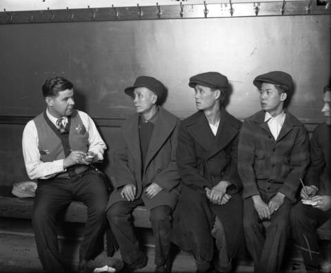 Police officer Frank Slak, from left, talks to May Woo, Lee Sun and Eng Foo Hang, three Chinese men arrested in the Tong (gang) Wars in Chinatown in 1927. The Tong Wars between the two rival gangs, On Leong and Hip Sing, led to violence in Chinatown.
