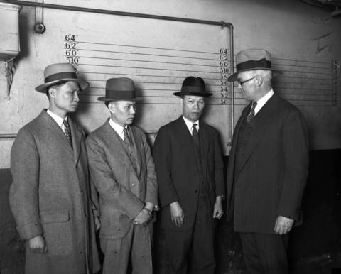 Capt. John Stege, right, talks to Wong Lee Woo, from left, Huie Sing and Chin Foy, generals of the Chinese gang Hip Sing tong in 1927. The Tong Wars between the two rival gangs, On Leong and Hip Sing, led to violence in Chinatown.