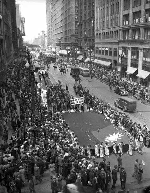 A parade of 6,000 Chinese-Americans travels through the Loop to protest the Japanese invasion of their homeland in 1938. The highlight of the parade was a huge flag that spectators tossed hundreds of coins into war refugee assistance.