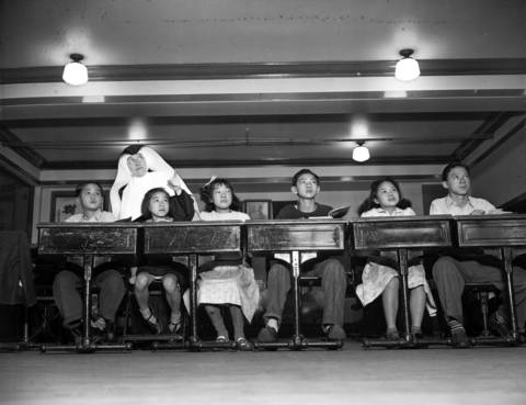 George Lee, 13, from left, Elsie Tong, 9, Mary Gin, 11, Rogan Moy, 14, and Frances Moy, 15, take class with Sister Gabriel at St. Therese Chinese Catholic School in Chinatown in 1941.