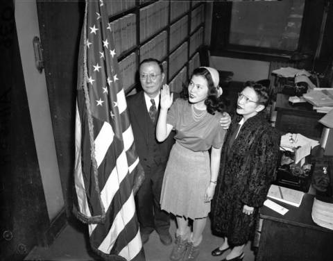 Katherine Jane Lee, 15, center, the first Chinese woman to become an American citizen since the repeal of the Chinese Exclusion Act, pledges allegiance to the flag during a naturalization ceremony before federal Judge John P. Barnes in 1944. Her grandfather, Edward Kan, left, who was an interpreter for the Department of Naturalization, and her mother, Mrs. Esther Lee, right, were with her in court.