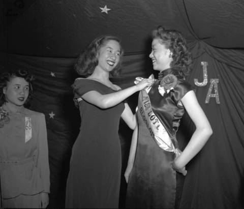 Florence Dea, 20, right, who won the Miss Lotus Blossom title, is crowned by last year's queen, Nancy Wong, 19, at the Lotus Blosssom Ball in the On Leong Merchant Association Building at 2216 S. Wentworth Ave. (now known as the Pui Tak Center) in Chinatown in 1949.